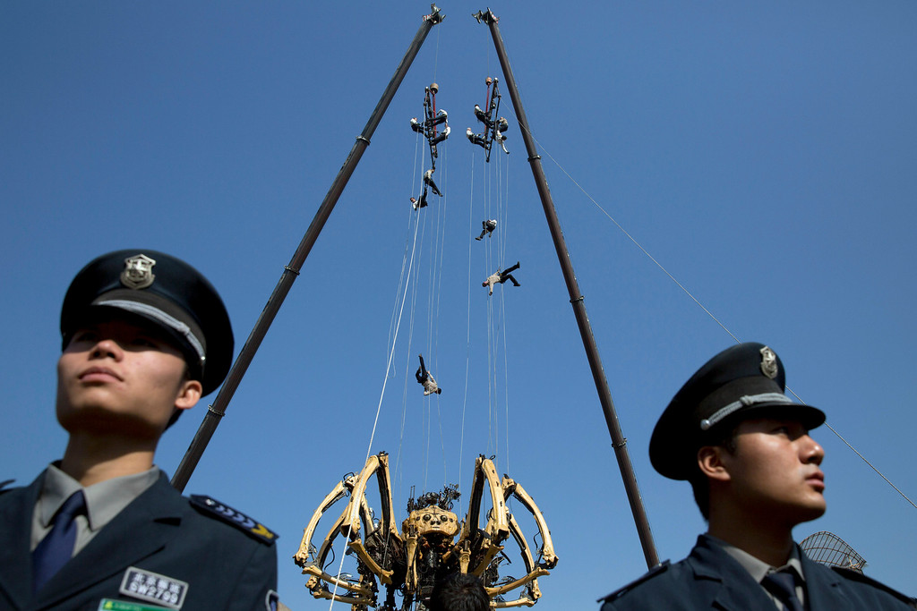 . Performers rappel down to the French production company La Machine\'s mechanical spider, also known as La Princesse, during a show held in front of the Bird\'s Nest Stadium in Beijing Friday, Oct. 17, 2014. A series of performances over three days will mark the climax of celebrations for the 50th anniversary of Sino-French diplomatic relations on Sunday, Oct 19.  (AP Photo/Ng Han Guan)