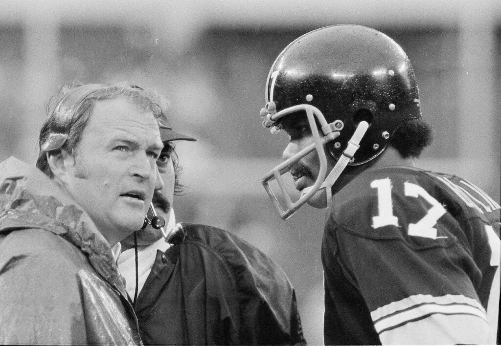 . Pittsburgh Steelers head coach Chuck Noll, left, with Terry Hanratty at his side, looks at the clock as he talks with quarterback Joe Gilliam during their 17-0 loss to the Oakland Raiders in Pittsburgh Sunday, Sept. 30, 1974. (AP Photo/Harry Cabluck)
