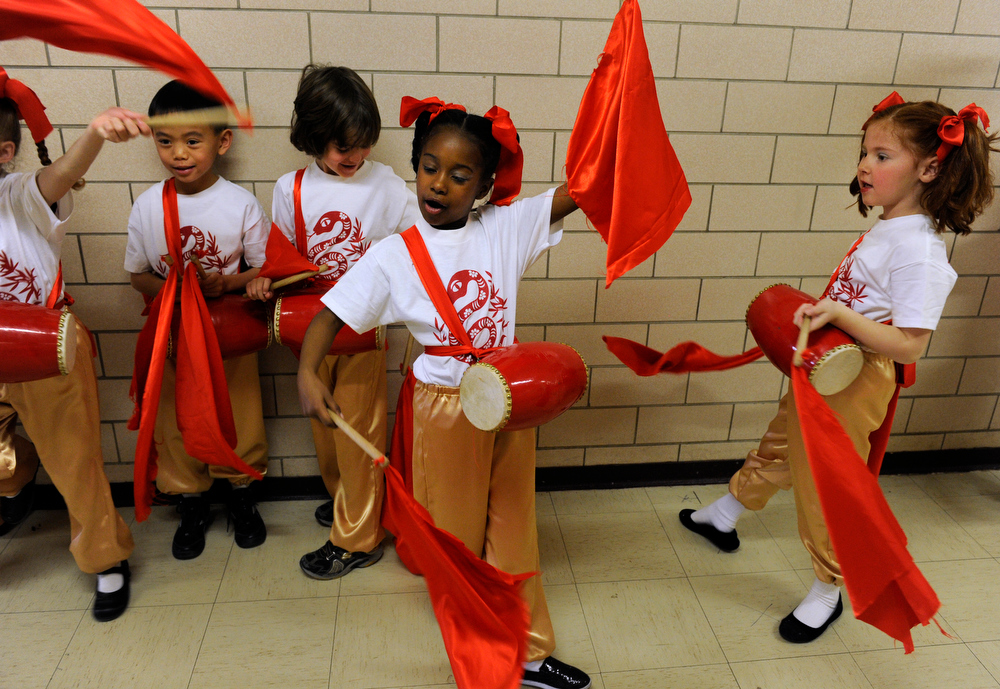 . First-graders practice their Yao Gu Wu dance in the hallway before their performance. Students at the Denver Language School ring in the Year of the Snake with their Chinese New Year celebration performance in the school auditorium. Kindergarteners through 4th grade perform traditional dances dressed in colorful Chinese costumes. According to the school principal, Chinese New Year is the most important of the traditional Chinese holidays. Families make way for  good luck by cleaning their homes symbolizing reconciliation and forgetting old grudges in exchange for peace and happiness. The Chinese New Year (Feb. 10) follows the Chinese 12 Zodiac Calendar Year designating 2013 the Year of the Snake. (Photo By Kathryn Scott Osler/The Denver Post)
