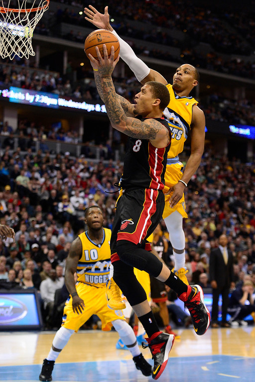 . Michael Beasley (8) of the Miami Heat drives on Randy Foye (4) of the Denver Nuggets during the second half of Miami\'s 97-94 win.  (Photo by AAron Ontiveroz/The Denver Post)
