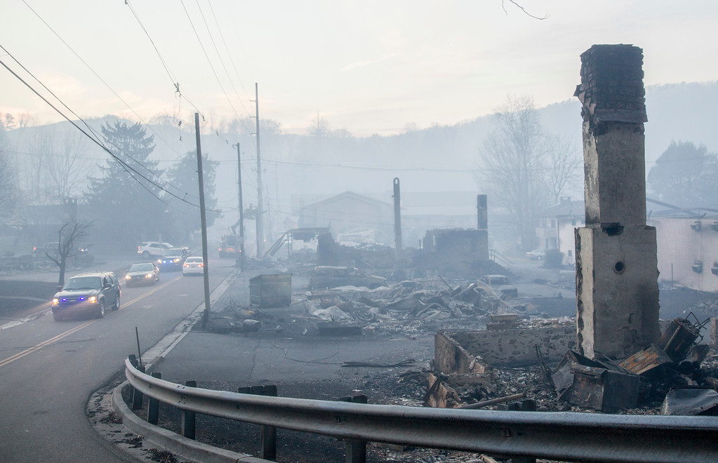 . Law enforcement vehicles drive through the smoke near structures destroyed by wildfires in Gatlinburg, Tenn., Tuesday, Nov. 29, 2016. The fatal wildfires swept over the tourist town the night before, causing widespread damage. (AP Photo/Erik Schelzig)