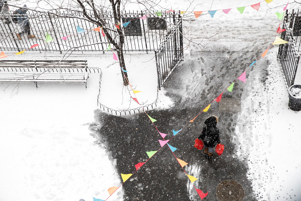 . A pedestrian walks through a snow covered park in lower Manhattan, Saturday, Jan. 7, 2017, in New York. (AP Photo/Mary Altaffer)
