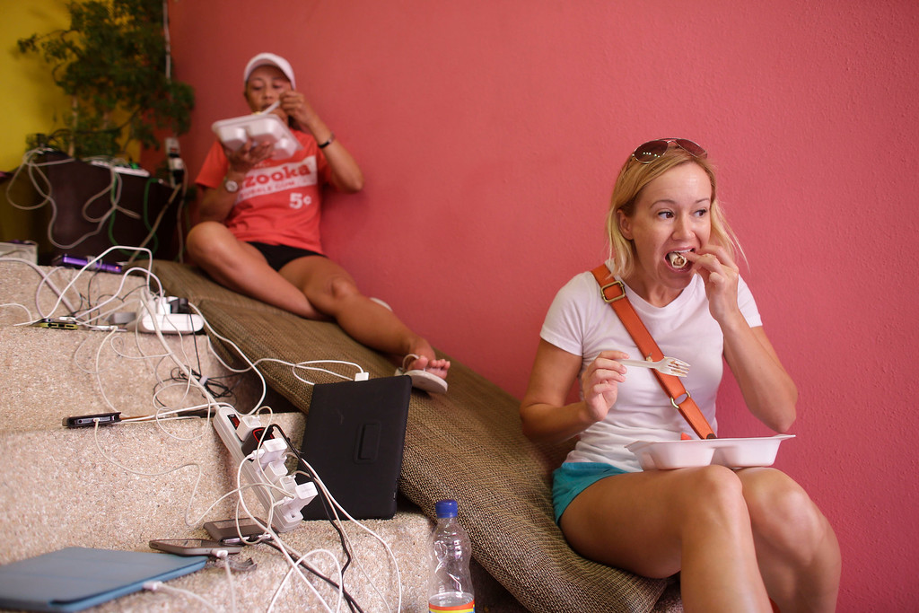 . Christina Hanson, right, of San Diego, California, eats her breakfast on the stairs of the Raintree Vacation Club resort as she charges her cell phone in one of the few plugs with electricity working off a generator after Hurricane Odile partially destroyed the resort in Los Cabos, Mexico,  Tuesday, Sept. 16, 2014. Desperate locals and tourists were in survival mode in the resort area of Los Cabos on Wednesday, with electrical and water service still out three days after Hurricane Odile made landfall as a monster Category 3 storm. (AP Photo/Victor R. Caivano)