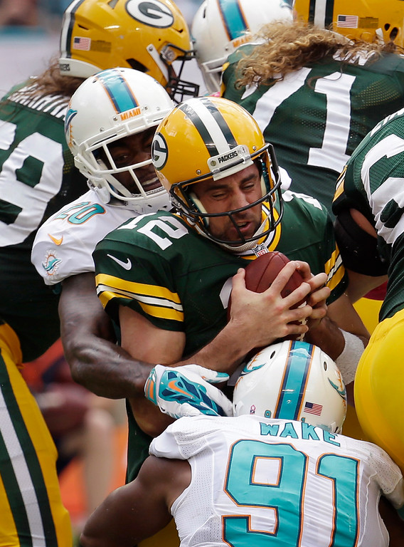 . Green Bay Packers quarterback Aaron Rodgers (12) is sacked by Miami Dolphins defensive end Cameron Wake (91) and free safety Reshad Jones (20) during the first half of an NFL football game, Sunday, Oct. 12, 2014, in Miami Gardens, Fla. (AP Photo/Lynne Sladky)