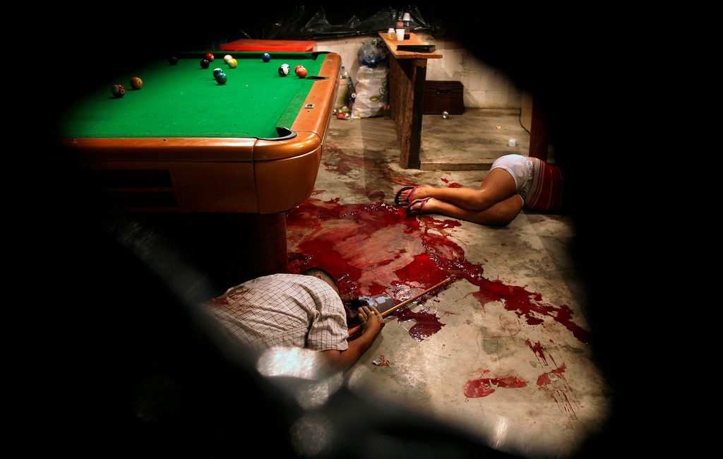 . In this March 11, 2012 file photo, the bodies of Lesbia Altamirano and Wilmer Orbera lie on the floor of a pool hall after being attacked by unidentified masked assailants in Choloma on the outskirts of San Pedro Sula, Honduras. This photo by Associated Press photographer Esteban Felix won the second place prize for the Contemporary Issues singles category in the World Press Photo 2013 photo contest. (AP Photo/Esteban Felix, File)