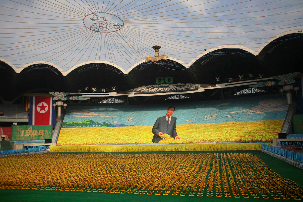 Description of . Thousands of North Koreans turn colored cards to form an image of North founder Kim Il Sung in a wheat field as gymnasts perform on the field below during a