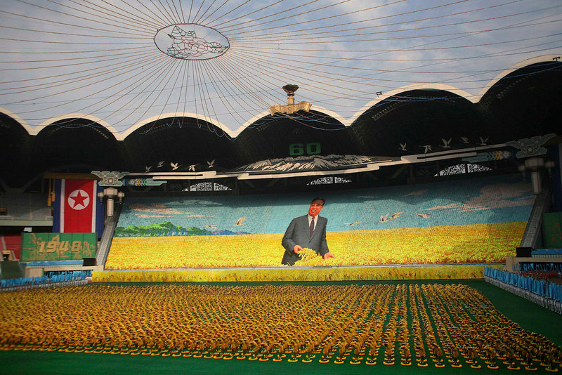 ". Thousands of North Koreans turn colored cards to form an image of North founder Kim Il Sung in a wheat field as gymnasts perform on the field below during a ""mass games\"" performance at a stadium in Pyongyang, North Korea, Friday, Sept. 19, 2008.  (AP Photo/David Guttenfelder)"