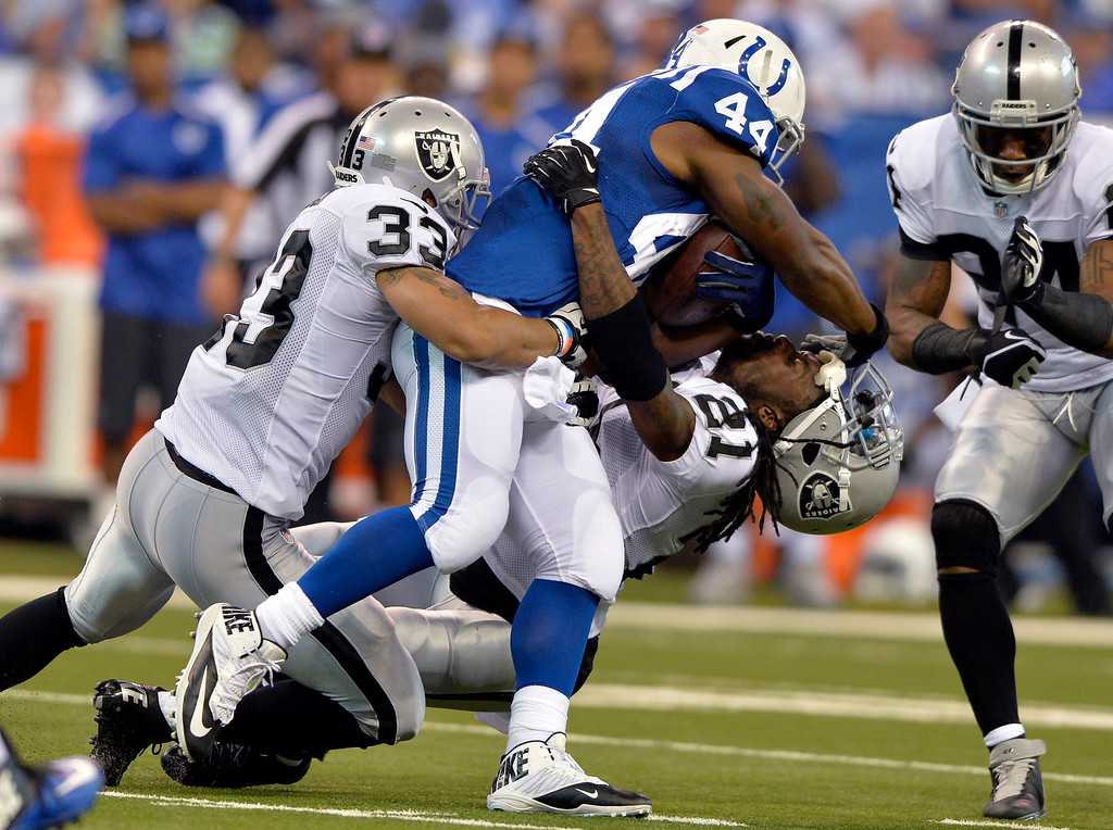 . Indianapolis Colts running back Ahmad Bradshaw (44) knock the helmet off of Oakland Raiders cornerback Mike Jenkins (21) as Bradshaw is tackled by strong safety Tyvon Branch during the second half of an NFL football game in Indianapolis, Sunday, Sept. 8, 2013. (AP Photo/Doug McSchooler)