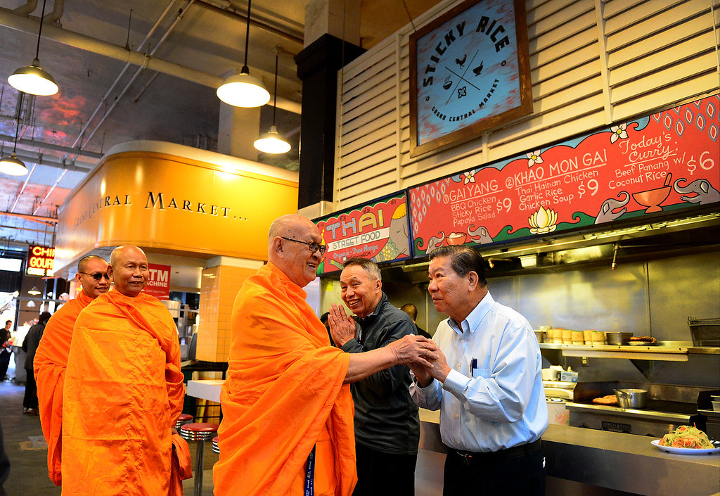 . Wat Thai Temple monks, of North Hollywood, approach Ben Utasee, left, and Suthin Tewasart as they arrive to bless the opening of Sticky Rice at Grand Central Market in downtown Los Angeles Monday, April 30, 2013. Sticky Rice, owned by David Tewasart, of Pasadena, is kicking off the openings of new restaurants at the market. (SGVN/Staff Photo by Sarah Reingewirtz)