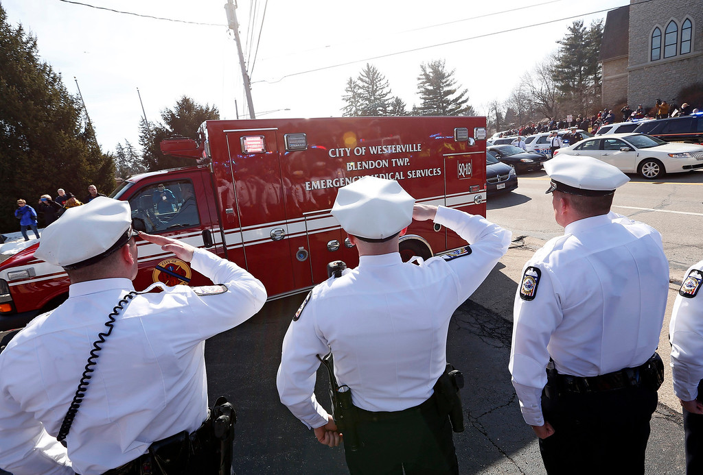 . Columbus Police honor guard members salute the ambulance carrying the body of Westerville Police officer Eric Joering during a procession transporting the bodies of Joering and Anthony Morelli from the Franklin County Coroners Office to the Hill and Moreland funeral homes in Westerville, Ohio, Monday, Feb. 12, 2018. (Adam Cairns/The Columbus Dispatch via AP)