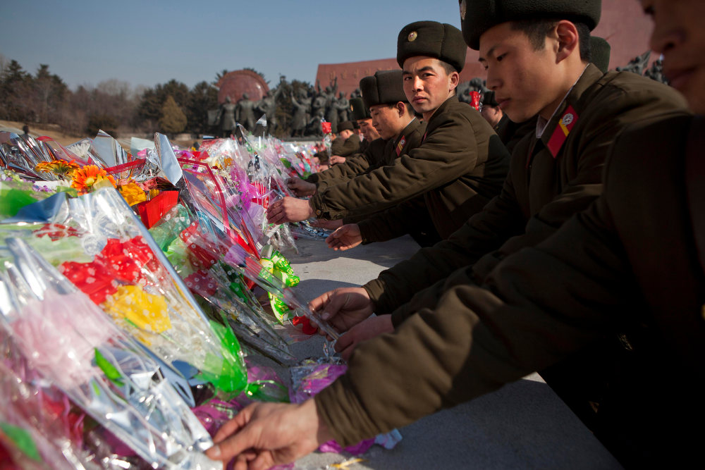 Description of . North Korean soldiers lay flowers at the base of bronze statues of the late leaders Kim Il Sung and Kim Jong Il to pay their respects in Pyongyang, North Korea on Saturday, Feb. 16, 2013. North Koreans turned out to commemorate what would have been the 71th birthday of Kim Jong Il who died on Dec. 17, 2011. (AP Photo/David Guttenfelder)