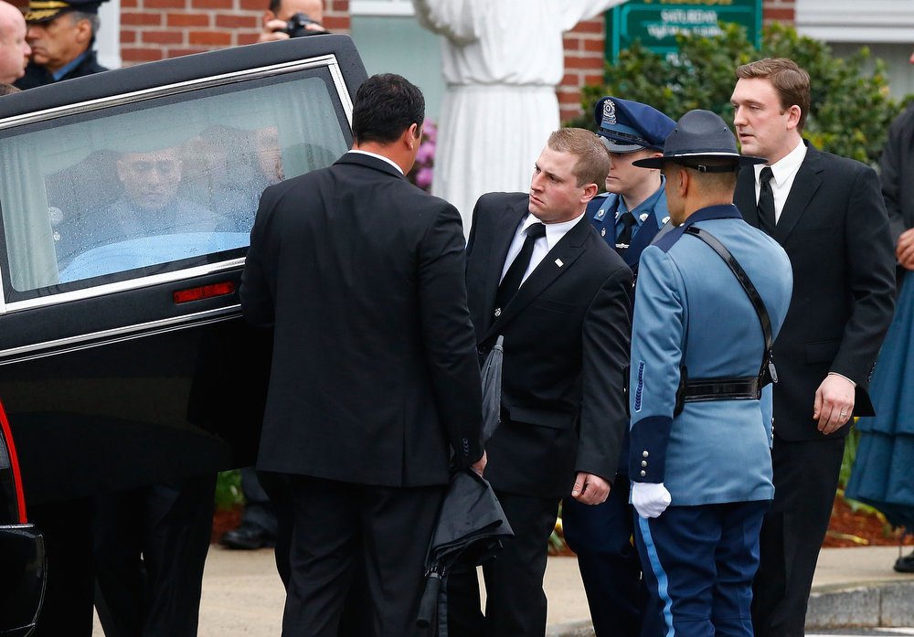 . Pallbearers carry the casket of slain Massachusetts Institute of Technology (MIT) police officer Sean Collier into the hearse following the funeral at St Patrick\'s Church on April 23, 2013 in Stoneham, Massachusetts. Collier was allegedly shot by the suspects in the Boston Marathon bombing, Dzhokhar A. Tsarnaev, 19, and his brother Tamerlan Tsarnaev, 26, after their identities were determined and a manhunt was launched.  Tamerlan Tsarnaev was subsequently shot and killed after a car chase and shootout with police and Dzhokhar Tsarnaev was apprehended on a boat parked on a residential property in Watertown, Massachusetts. The bombing, on April 15 at the finish line of the marathon, killed three people and wounded at least 170.  (Photo by Jared Wickerham/Getty Images)
