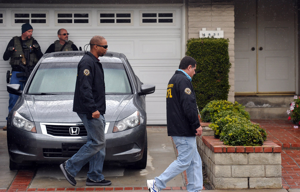 . U.S. Marshals stand with weapons ready outside of what is believed to be Christopher Dorner\'s mother\'s La Palma home as Orange County Regional Computer Forensics Laboratory investigators enter the home on Friday February 8, 2013. Various agencies have arrived to lend assistance at the home. (SGVN/Staff Photo by Keith Durflinger)