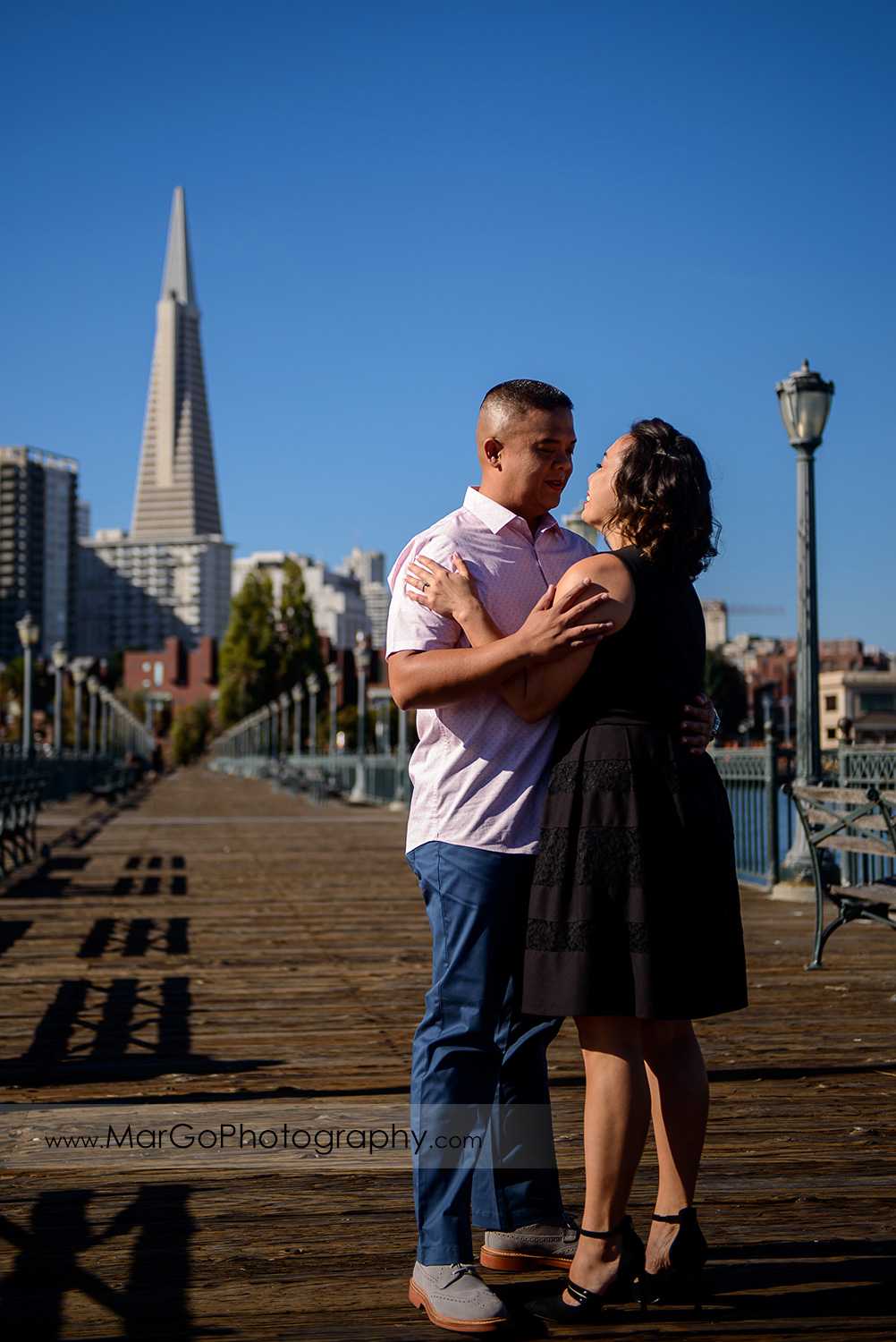 engagement session at Pier 7 in San Francisco - couple hugging with the Transamerica Pyramid in the background