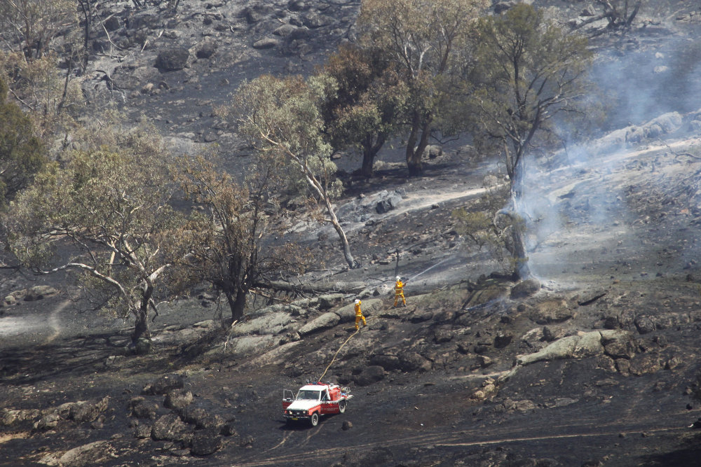 """. Fire fighters battle a grass fire in Oura, near Wagga Wagga in New South Wales on January 8, 2013. Bushfires raged across Australia\'s most populous state on January 8, fanned by intense heat and high winds in \""""catastrophic\"""" conditions that have put thousands of firefighters on high alert.  AFP PHOTO / AAP / Lukas Coch"""