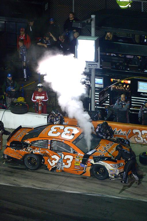 . Brian Scott (33) gets work done on his car in the pits as smoke pours out during the NASCAR Daytona 500 auto race at Daytona International Speedway in Daytona Beach, Fla., Sunday, Feb. 23, 2014. (AP Photo/Phelan M. Ebenhack)