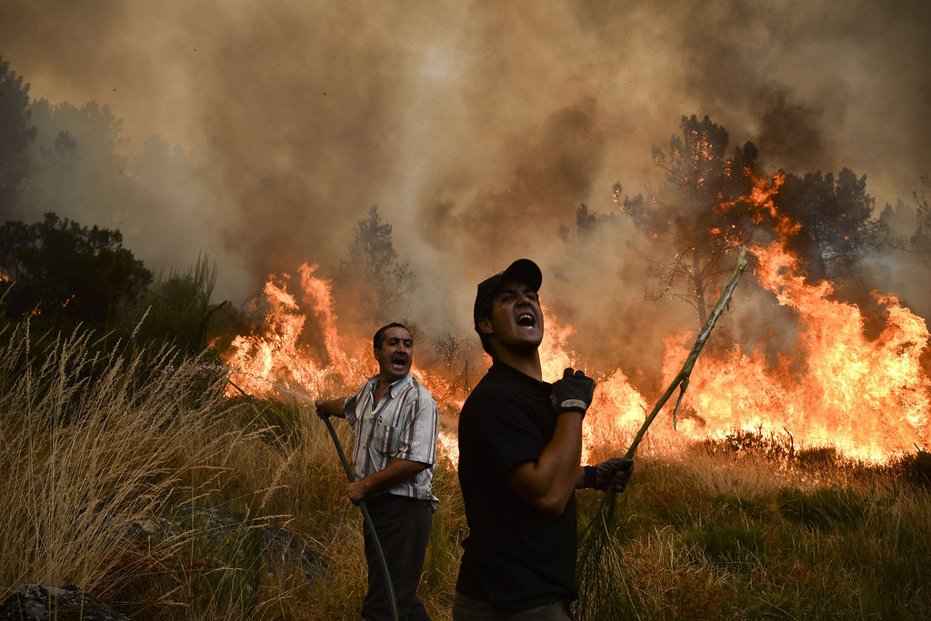 . Locals shout as they try to extinguish a wildfire in Caramulo, central Portugal on August 29, 2013.    AFP PHOTO / PATRICIA DE MELO  MOREIRA/AFP/Getty Images