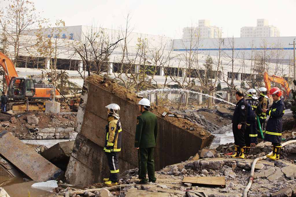 . Rescuers work at the site of an oil pipeline explosion in Qingdao, China, 22 November 2013. An explosion killed at least 35 people on 22 November as workers were repairing a crack in an oil pipeline in the eastern Chinese city of Qingdao, reports said.  EPA/LI LI