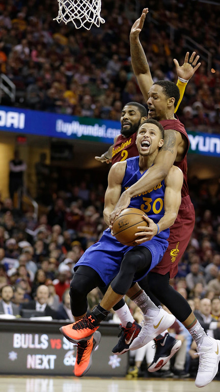 . Golden State Warriors\' Stephen Curry, front to back is fouled by Cleveland Cavaliers\' Channing Frye as Kyrie Irving watches in the second half of an NBA basketball game, Sunday, Dec. 25, 2016, in Cleveland. (AP Photo/Tony Dejak)