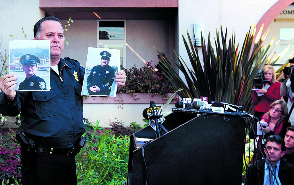 . Santa Cruz Police Chief Kevin Vogel holds pictures of slain detectives Elizabeth Butler and Loran \'Butch\' Baker during a press conference Wednesday morning. (Shmuel Thaler/Sentinel)