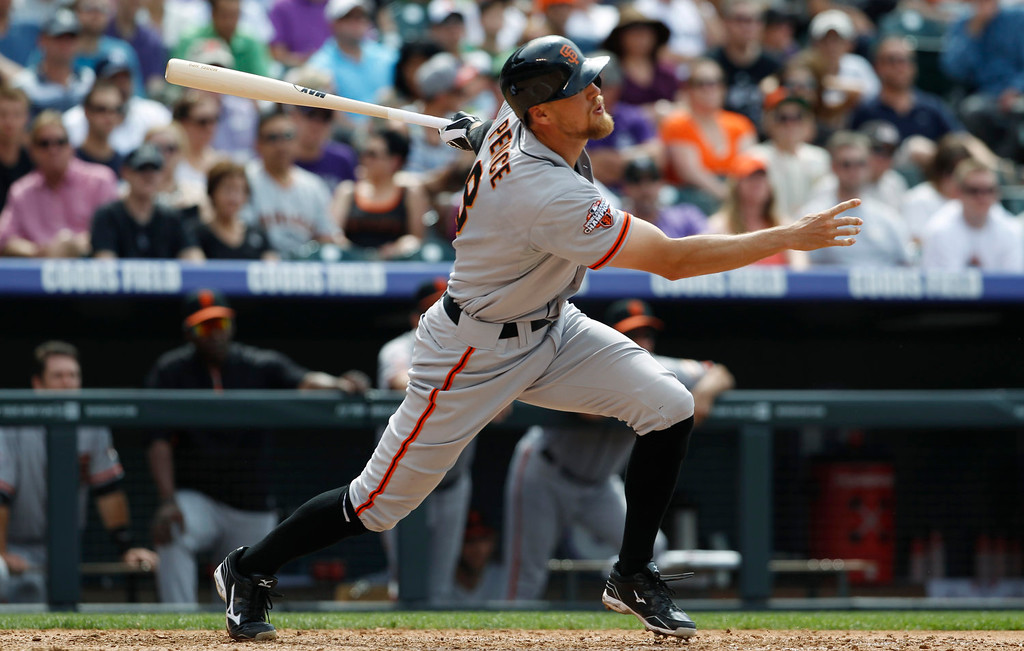 . San Francisco Giants\' Hunter Pence follows the flight of his two-run home run against the Colorado Rockies in the fifth inning of a baseball game in Denver on Sunday, June 30, 2013.  (AP Photo/David Zalubowski)