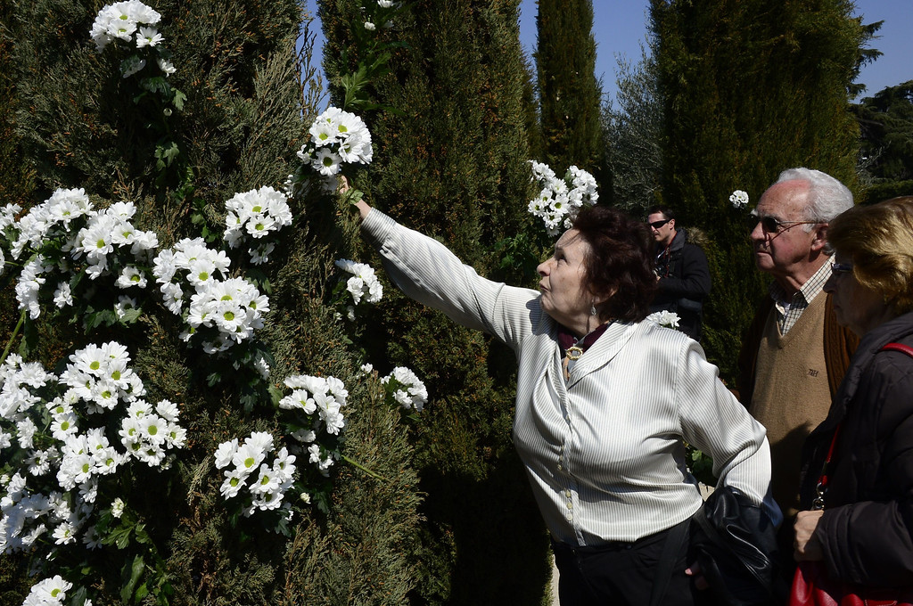 . People place flowers into trees during a commemoration ceremony in held in the Rememberance Garden of Madrid\'s Retiro Park on March 11, 2014 for the victims of the Madrid train bombings marking the10th year anniversary of the attacks that claimed 191 lives and injured more than 1800 others. On March 11, 2004 at 7:40 am, 10 bombs exploded on board four packed commuter trains in Madrid in an attack claimed by the Al-Qaeda terror network, which said they were punishment for Spain\'s role in the US-led invasion of Iraq. JAVIER SORIANO/AFP/Getty Images