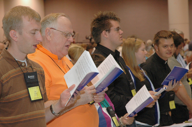 Voting members join in morning prayer and song on Thursday.