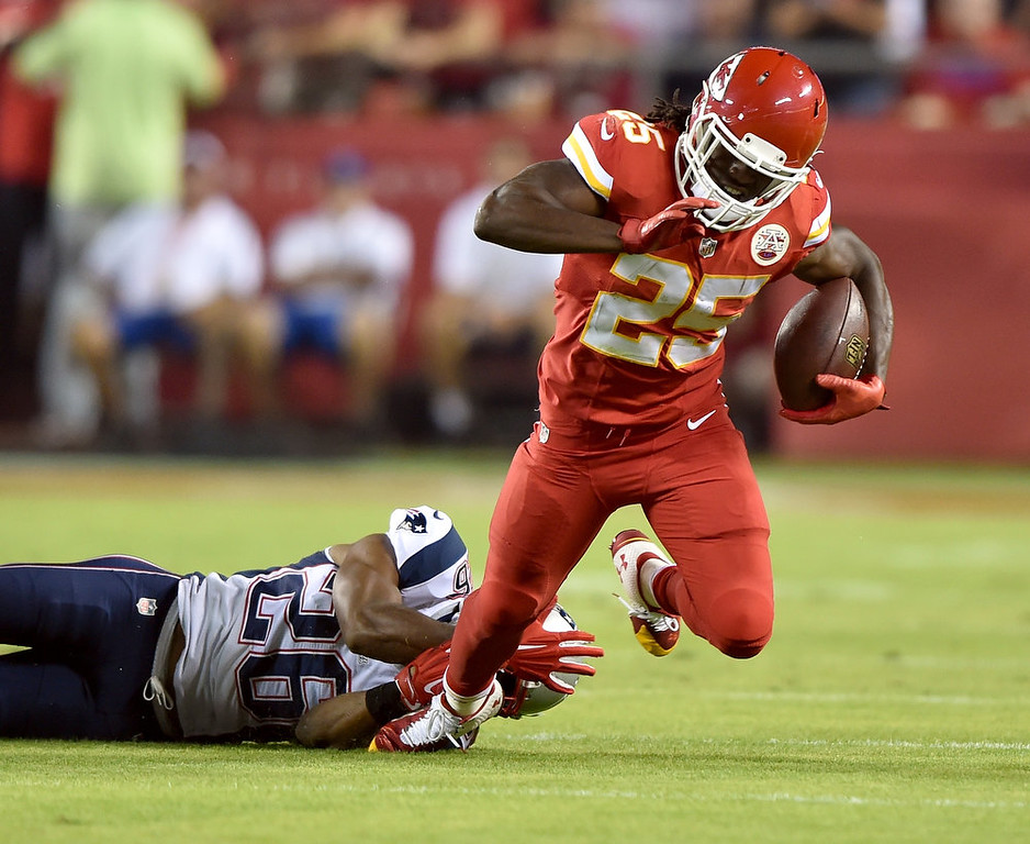 . Jamaal Charles #25 of the Kansas City Chiefs is tripped up by Logan Ryan #26 of the New England Patriots during the first quarter at Arrowhead Stadium on September 29, 2014 in Kansas City, Missouri.  (Photo by Peter Aiken/Getty Images)