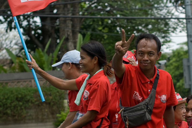 Man holding out peace sign to camera during Red Shirt Protest in Thailand