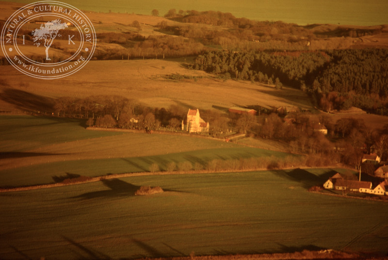 Farmland west of Ravlunda church - with plantations, buildings and prehistoric remains. Experimentally photographed with yellow filter (20 November, 1988). | LH.0265