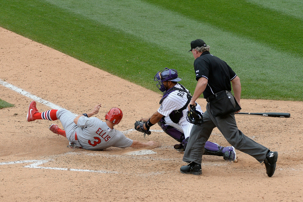. St. Louis Cardinals second baseman Mark Ellis (3) slides under the tag of Colorado Rockies catcher Wilin Rosario (20) scoring on a double by St. Louis Cardinals second baseman Daniel Descalso (33) in the eighth inning to tie the game at 6-6 June 25, 2014 at Coors Field. (Photo by John Leyba/The Denver Post)