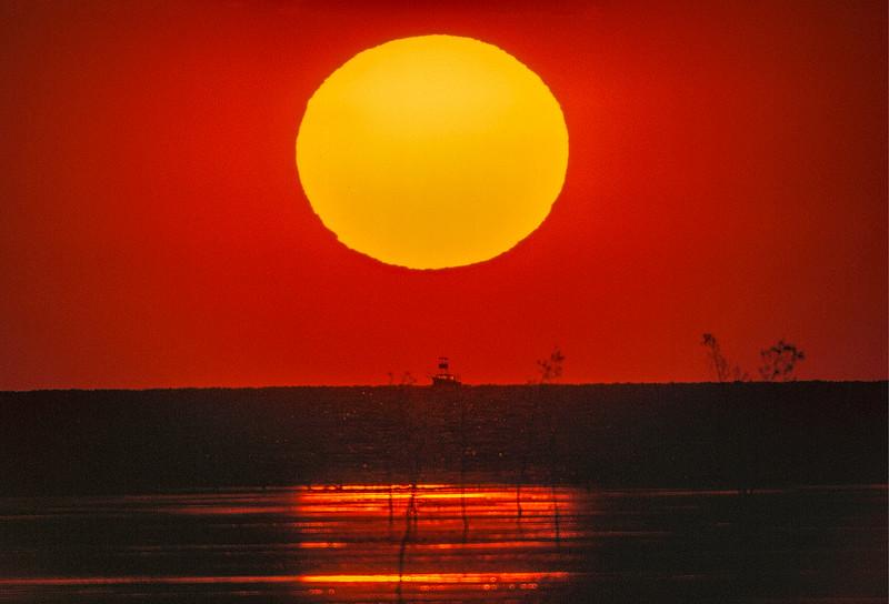 Sun over Cape Cod shore and charter fising boat.