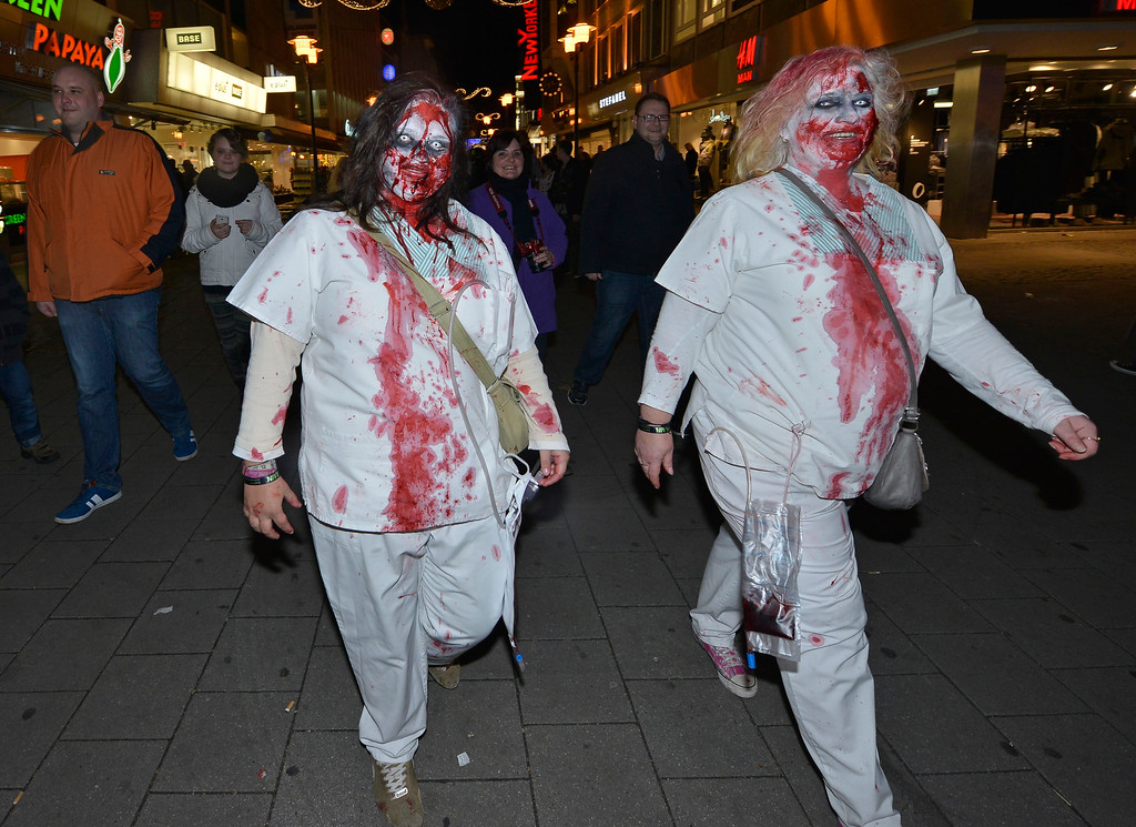 . Two women  dressed as zombies walk around the train station at the city center of Essen, western Germany, Thursday, Oct. 31, 2013. The so called \'zombie walk\' with about 1000 horror fans has become a tradition in the city on Halloween. (AP Photo/Martin Meissner)