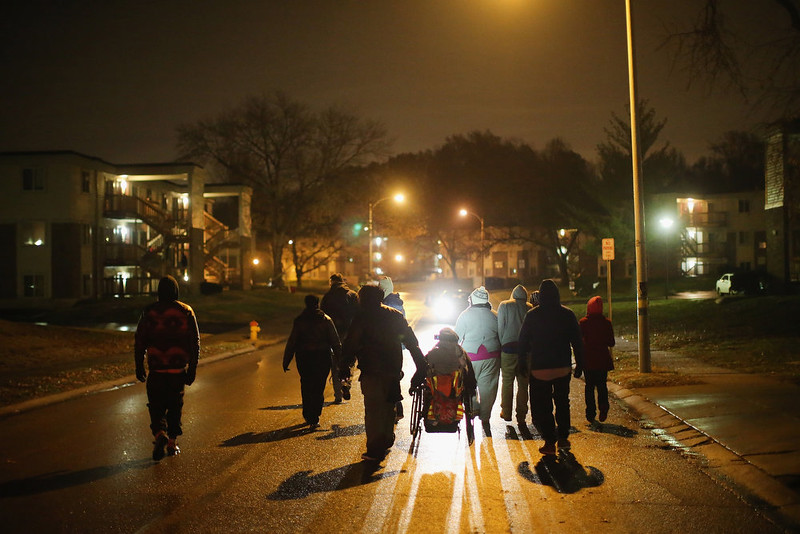 . Demonstrators protesting the shooting death of Michael Brown walk near the spot where he was shot on November 21, 2014 in Ferguson, Missouri. Brown, an 18-year-old black man, was killed by Darren Wilson, a white Ferguson police officer, on August 9. A grand jury is expected to decide soon if Wilson should be charged in the shooting..  (Photo by Scott Olson/Getty Images)