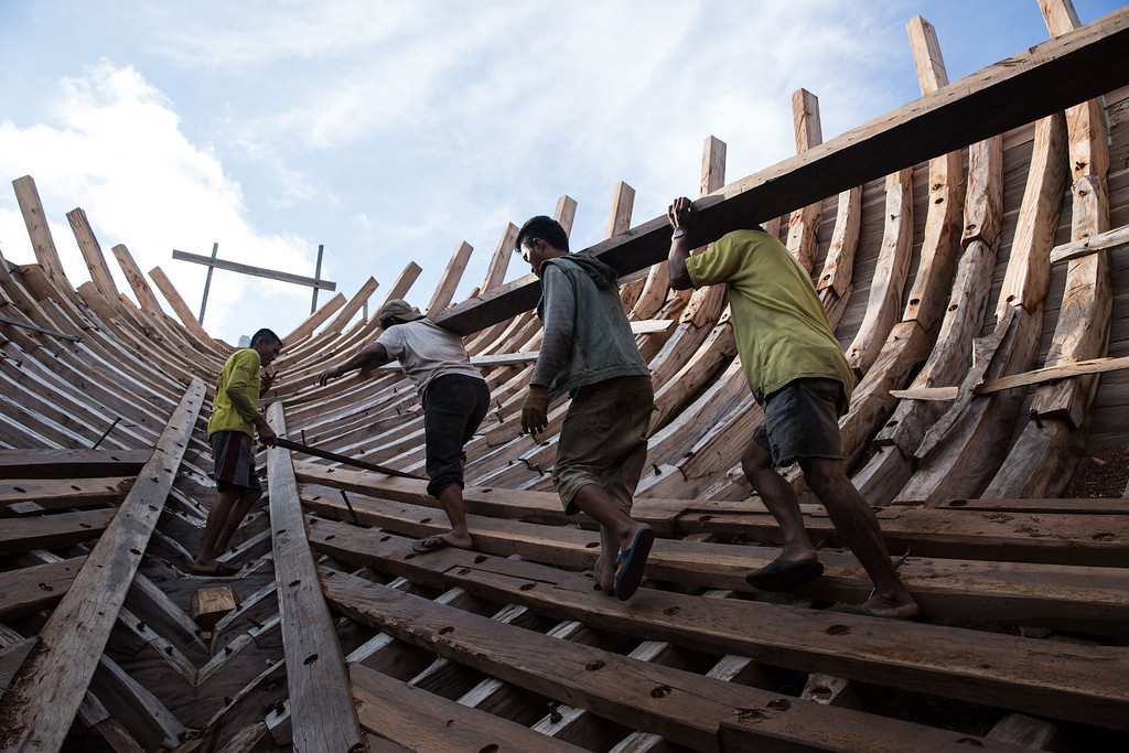 . Buginese men carry a wooden block in the hull of phinisi at Tanjung Bira Beach on May 2, 2014 in Bulukumba, South Sulawesi, Indonesia.  (Photo by Agung Parameswara/Getty Images)