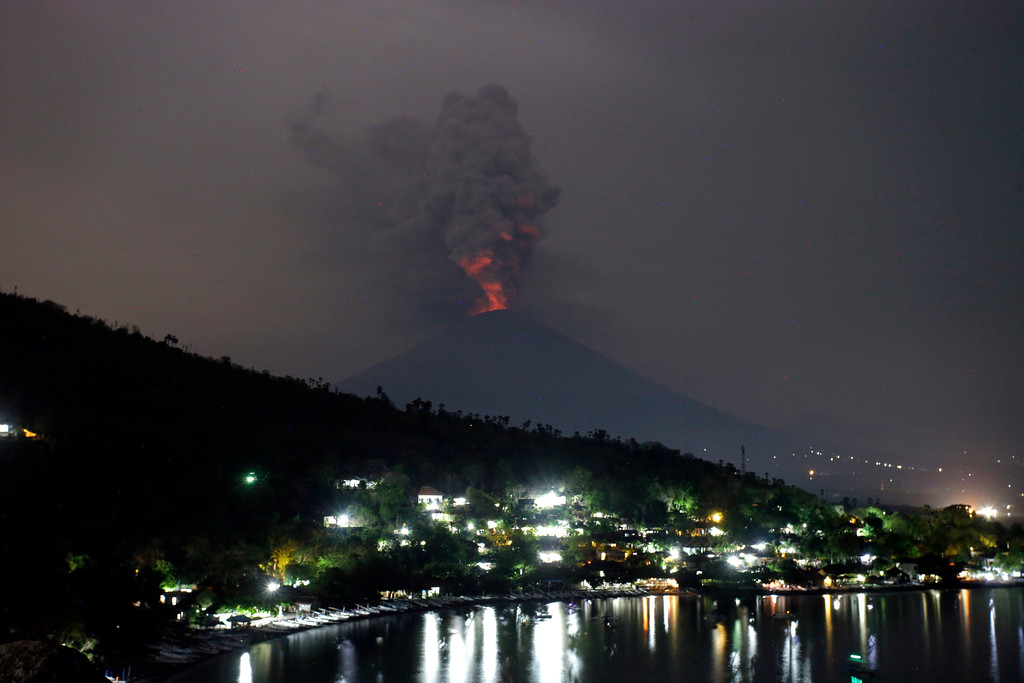 . A view of the Mount Agung volcano erupting in Karangasem, Bali, Indonesia, Monday, Nov. 27, 2017. Indonesia authorities raised the alert for the rumbling volcano to highest level on Monday and closed the international airport on the tourist island of Bali stranding thousands of travelers. (AP Photo/Firdia Lisnawati)