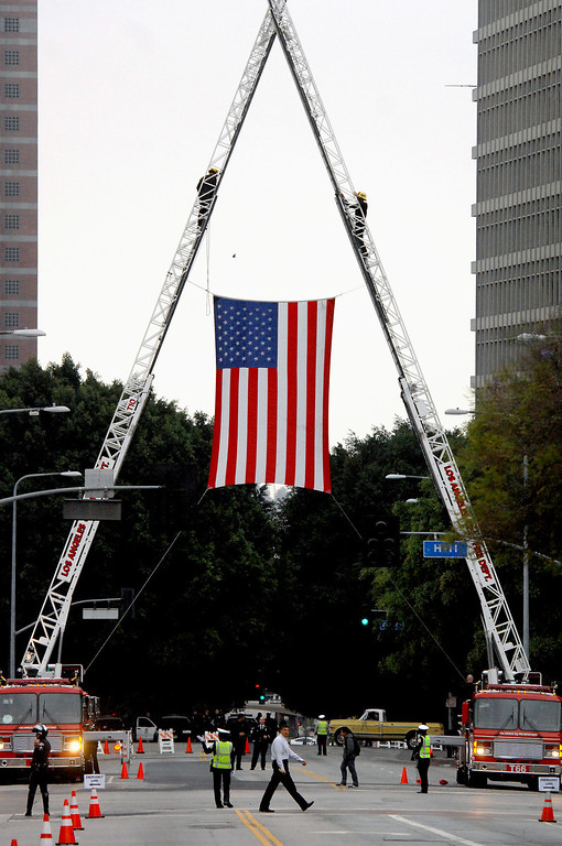 . LAFD hangs a flag over Temple Street in downtown L.A., Tuesday, April 22, 2014, for the funeral mass for LAPD motorcycle officer Chris Cortijo. (Photo by Michael Owen Baker/L.A. Daily News)