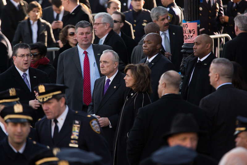 . Police Commissioner Bill Bratton (C) arrives with his wife Rikki Klieman outside the funeral of slain New York Police Department (NYPD) officer Rafael Ramos at the Christ Tabernacle Church on December 27, 2014 in the Glenwood section of the Queens borough of New York City. Ramos was shot, along with Police Officer Wenjian Liu while sitting in their patrol car in an ambush attack in Brooklyn on December 20. Thousands of fellow officers, family, friends and Vice President Joseph Biden arrived at the church for the funeral.  (Photo by Kevin Hagen/Getty Images)