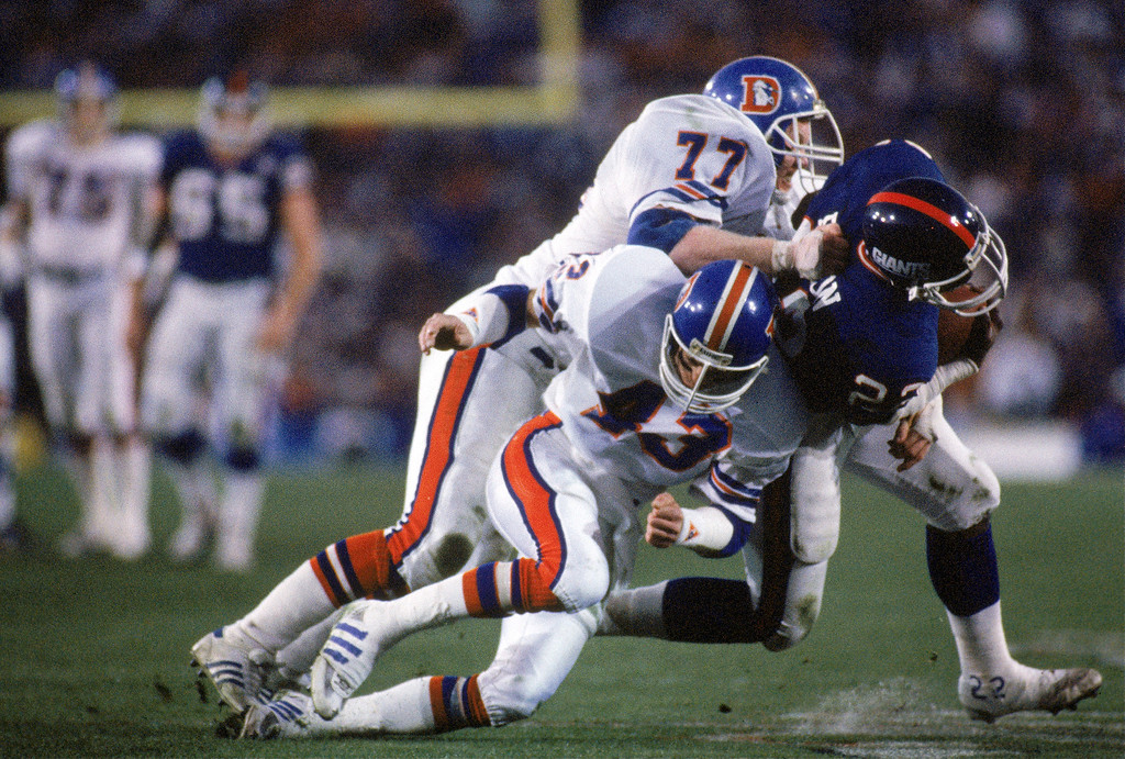 . Linebacker Karl Mecklenburg #77 and defensive back Steve Foley #43 of the Denver Broncos take down running back Lee Rouson #23 of the New York Giants during Super Bowl XXI at the Rose Bowl on January 25, 1987 in Pasadena, California.    (Photo by George Rose/Getty Images)