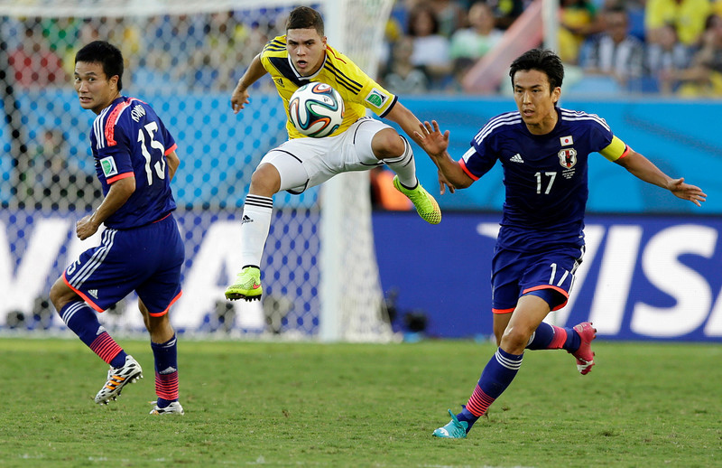 . Colombia\'s Juan Quintero, center, gets to the ball ahead of Japan\'s Yasuyuki Konno, left, and Makoto Hasebe during the group C World Cup soccer match between Japan and Colombia at the Arena Pantanal in Cuiaba, Brazil, Tuesday, June 24, 2014. (AP Photo/Thanassis Stavrakis)