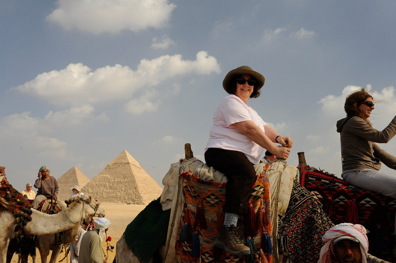 Renee Mirsky on a camel at the Giza Plateau.  The Great Pyramid of Khufu is to the left.  The Pyramid of Khafre is to the right of the Great Pyramid of Khufu.  _D7C8051