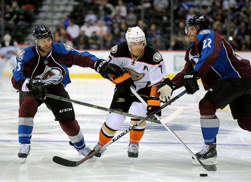 . Colorado Avalanche center Maxime Talbot, left, and Colorado defenseman Zach Redmond, right, defend against Anaheim Ducks center Andrew Cogliano, center, in the second period of an NHL preseason hockey game Monday, Sept. 22, 2014, in Denver. (AP Photo/Chris Schneider)
