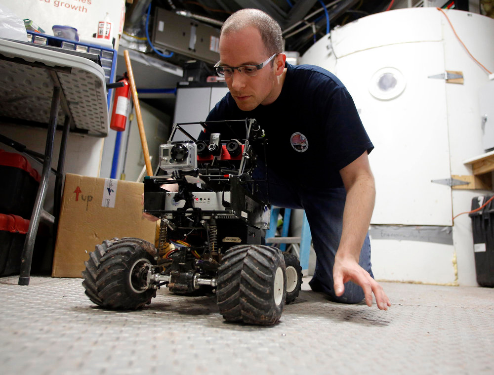 . Matt Cross, an engineer with Crew 125 EuroMoonMars B mission, works on a rover at the Mars Desert Research Station (MDRS) outside Hanksville in the Utah desert March 3, 2013.  REUTERS/Jim Urquhart