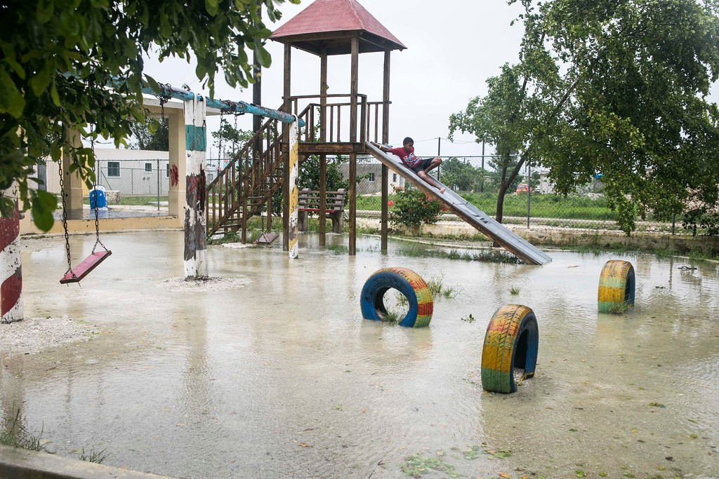 . A boy plays at a flooded playground close to a shelter, while Hurricane Maria approaches the coast of Bavaro, Dominican Republic, Wednesday, Sept. 20, 2017. The U.S. National Hurricane Center says Maria has lost its major hurricane status, after raking Puerto Rico. But forecasters say some strengthening is in the forecast and Maria could again become a major hurricane by Thursday. (AP Photo/Tatiana Fernandez)