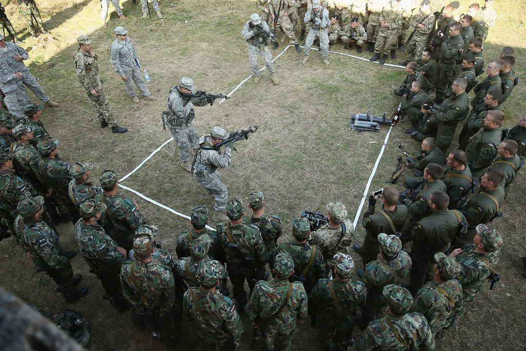 ". Members of the U.S. Army 173rd Airborne Brigade demonstrate urban warfare techniques as Bulgarian (bottom) and Ukrainian soldiers look on on the second day of the ""Rapid Trident\"" NATO military exercises on September 16, 2014 near Yavorov, Ukraine.  (Photo by Sean Gallup/Getty Images)"