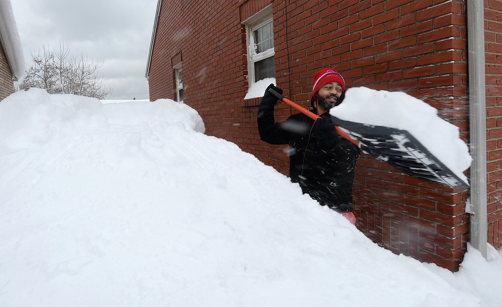 . Patrick Harden clears snow from the roof of his car on Tuesday, Dec. 26, 2017, in Erie, Pa. The National Weather Service office in Cleveland says Monday\'s storm brought 34 inches of snow, an all-time daily snowfall record for Erie. Another 19 inches fell before dawn Tuesday, making the greatest two-day total in commonwealth history. (Greg Wohlford/Erie Times-News via AP)