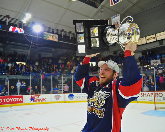 Grand Rapids Griffins Brennan Evans (44), who scored the game winning goal, hoists the Calder Cup at the Onondaga County War Memorial in Syracuse, New York on Tuesday, June 18, 2013 after his team defeated the Syracuse Crunch in a Best-of-7 game series, 4 to 2.