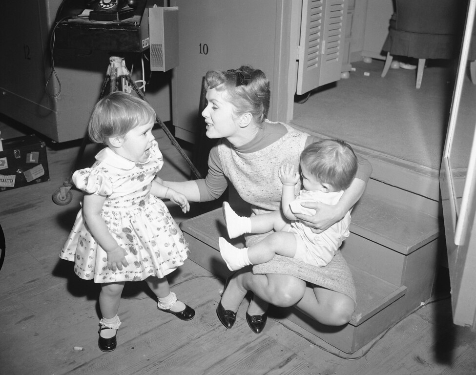""". Working long hours on the set of \""""Say One For Me,\"""" so she can fly to Spain and start another movie, actress Debbie Reynolds is visited at the studio by her children, Carrie 2½, and one-year-old Todd on Feb 27, 1959. Because Debbie has been away from the children so much the last couple of weeks, studio officials arranged to have the youngsters visit their mother during working hours. Debbie plans to leave on March 3 for Madrid. The youngsters will stay with Debbie\'s parents while their actress mother is overseas. (AP Photo)"""