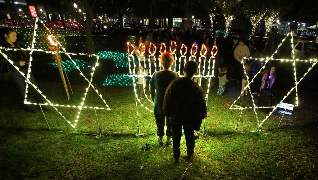 . Shari Albert, with her son Corey, 10, checkouts the giant Menorah as members of the central Florida Jewish community and residents of Winter Garden, Fla., gathered for the first-ever Menorah lighting ceremony for Hanukkah in the downtown of the city near Orlando, Tuesday, Dec. 12, 2017. (Joe Burbank/Orlando Sentinel via AP)