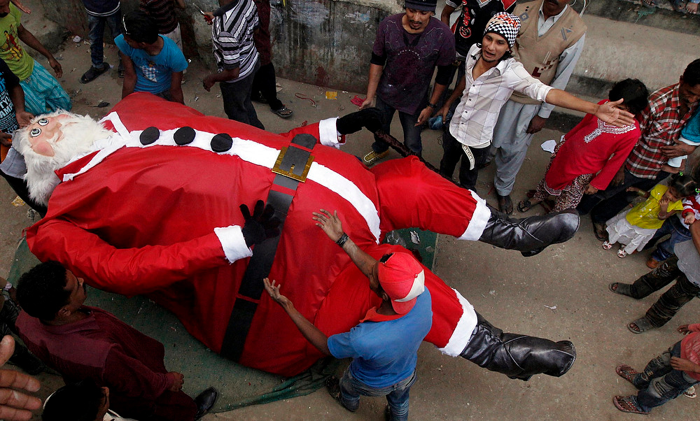 Description of . Residents lift up a Santa Claus figurine which they decorated in an alley as part of Christmas celebrations in Karachi on December 24, 2012. REUTERS/Akhtar Soomro